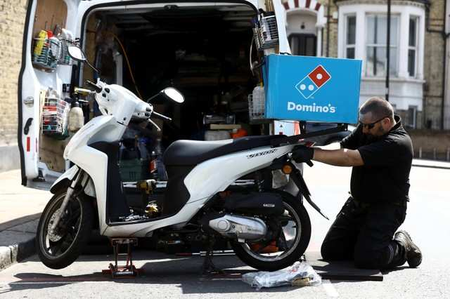 A call out mechanic fixes a Dominos delivery scooter in the Clapham district of London, Britain June 8, 2018. REUTERS/Simon Dawson