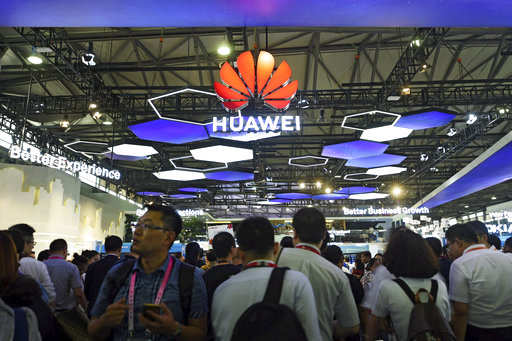 Visitors tour the Huawei exhibition booth during the Mobile World Congress in Shanghai, China, Wednesday, June 27, 2018. A Huawei executive says Australia could damage its economic future if it bans the Chinese telecommunication giant from the nation's next-generation mobile network technology. (Chinatopix via AP)