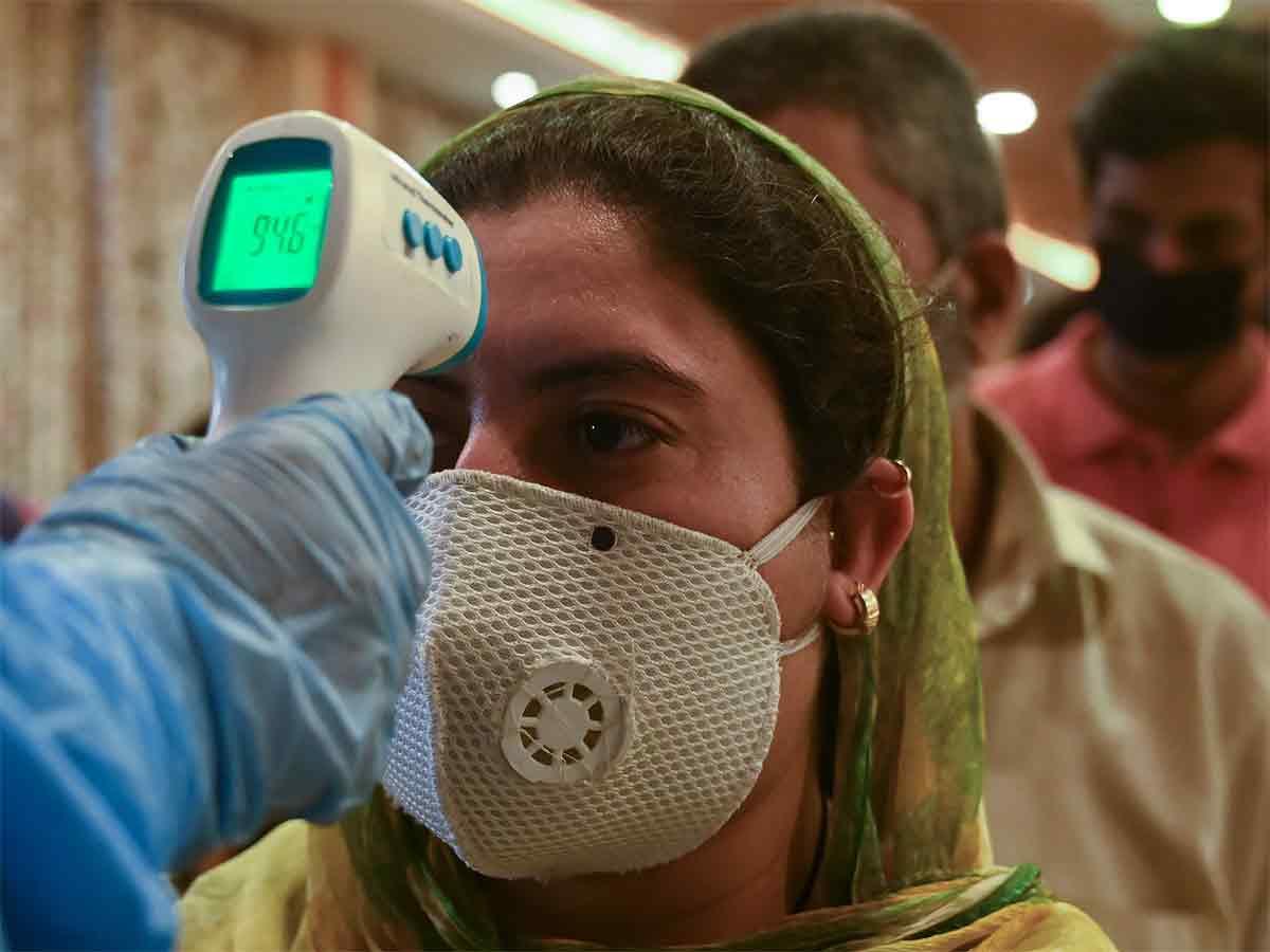 Un médecin vérifie la température corporelle des travailleurs migrants et des propriétaires d'entreprise à leur retour de Goa à la périphérie de Srinagar le 13 mai 2020. (AFP Photo)