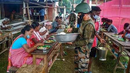 Le personnel militaire sert un repas aux populations locales touchées par les incendies de champs de pétrole à Bagdan, lors de la fermeture en cours de COVID-19, dans le comté de Tinsukia