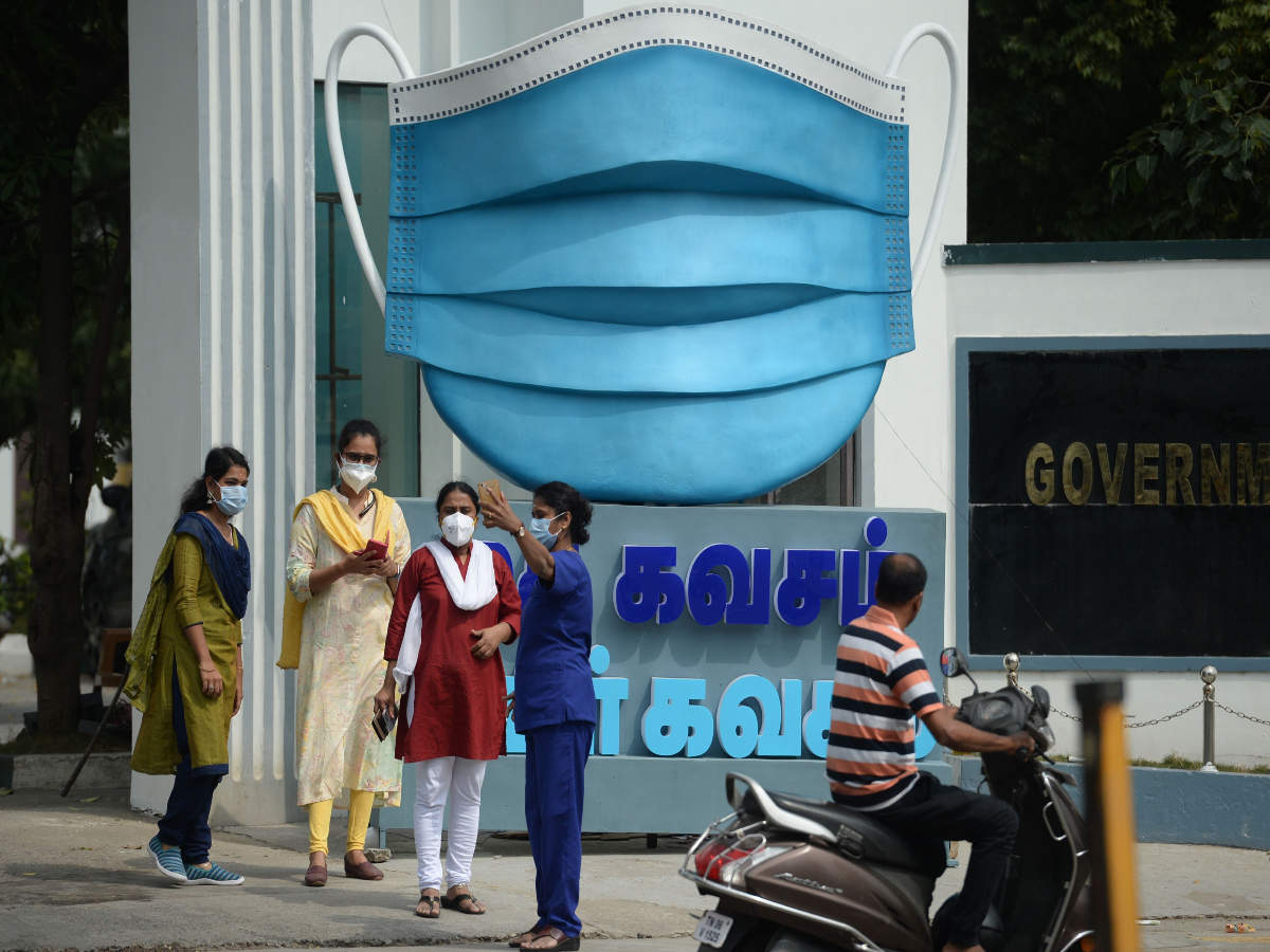 Medical staff take pictures beside a large replica facemask displayed as an awareness campaign against the Covid-19 coronavirus, in Chennai (AFP)