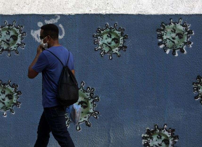 A man walks next to graffiti depicting viruses with the face of Brazil's President Jair Bolsonaro, amid the coronavirus disease outbreak in Rio de Janeiro, Brazil