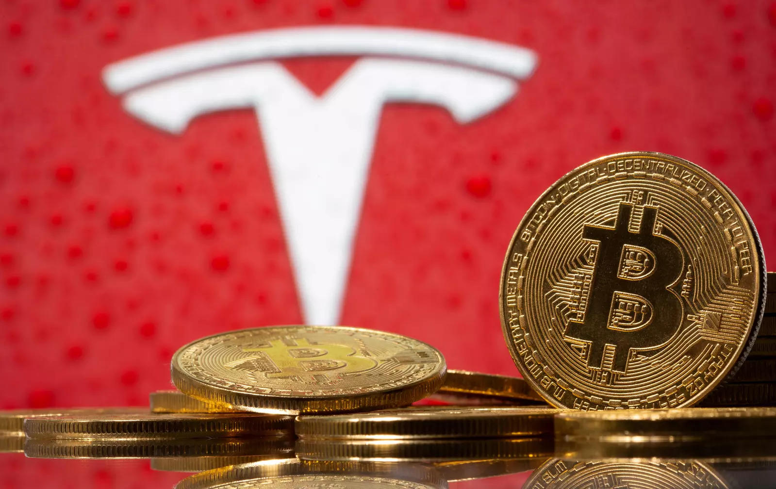 Representations of virtual currency Bitcoin are seen in front of Tesla logo in this illustration taken, February 9, 2021. REUTERS/Dado Ruvic/File Photo