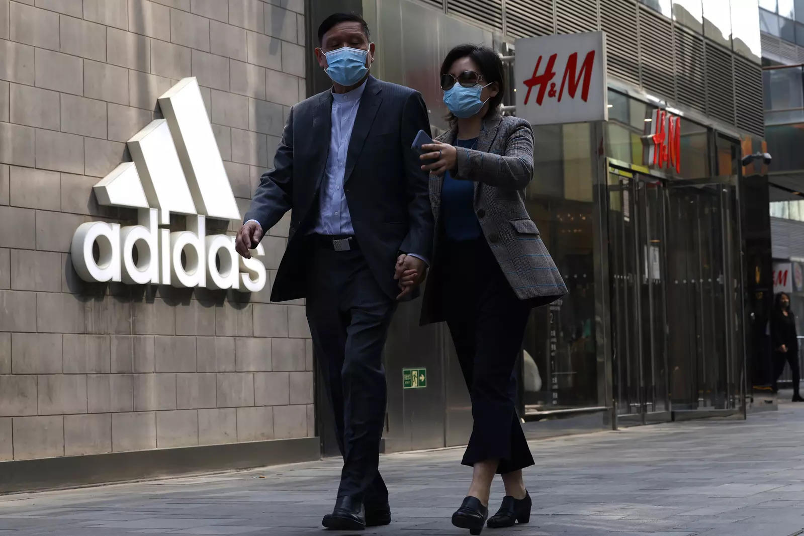 Visitors to a mall shopping area pass by Adidas and H&M stores in Beijing (File photo/AP)