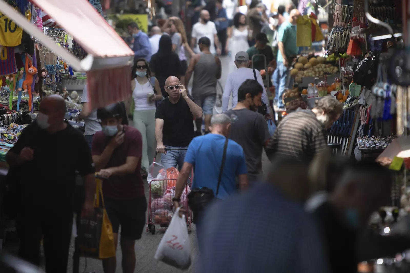 Israelis walk in a busy market in Tel Aviv on Sunday, April 18, 2021. Israel has lifted a public mask mandate in the latest easing of coronavirus restrictions following its mass vaccination drive.