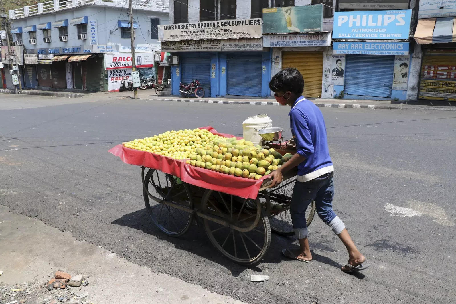 Jammu: A fruit vendor pushes his cart through a deserted market area as he searches for customers, during COVID-induced weekend lockdown in Jammu. (PTI Photo)(